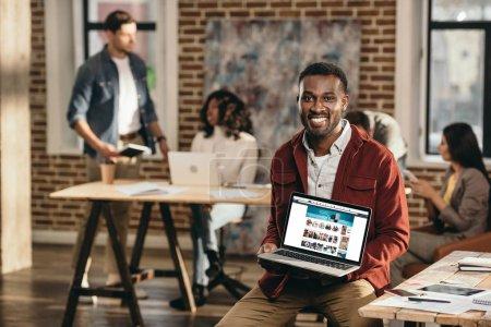 africano americano casual hombre de negocios celebración de ordenador portátil con el sitio web de compras y colegas que trabajan detrás en la oficina loft