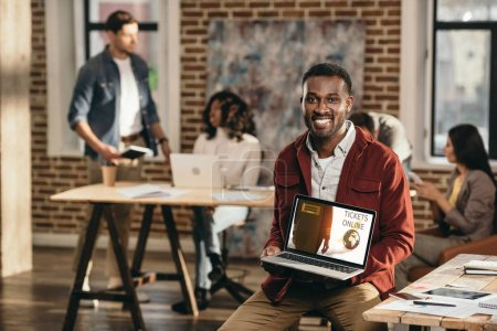 african american casual businessman holding laptop with online tickets web site and colleagues working behind in loft office