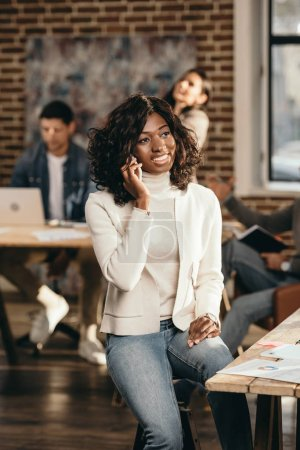 Photo for Cheerful african american casual businesswoman sitting and talking on smartphone in loft office with colleagues working behind - Royalty Free Image