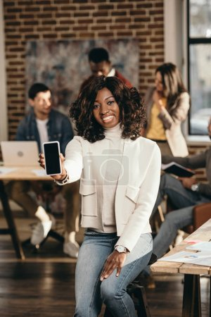 smiling african american casual businesswoman pointing at smartphone with blank screen in loft office with colleagues behind