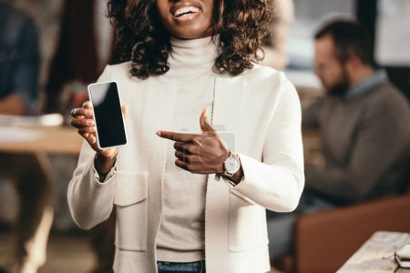 cropped view of smiling african american casual businesswoman pointing at smartphone with blank screen with colleagues behind