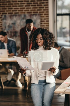 serious african american casual businesswoman holding papers with colleagues working behind in loft office