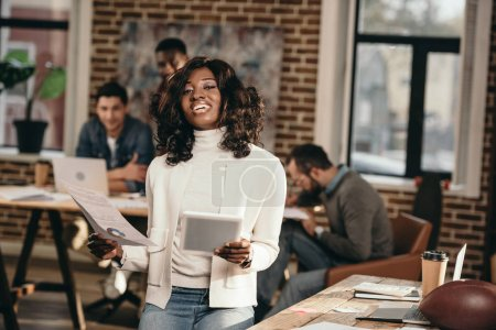 smiling african american casual businesswoman holding papers with colleagues working behind in loft office