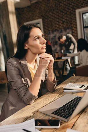 Photo for Pensive business woman sitting at desk with laptop and working at loft office with colleagues on background - Royalty Free Image