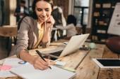 """Постер, картина, фотообои """"красивые успешный бизнес женщина, сидя за столом с ноутбуком и работает над проектом офисе чердак с коллегами на фоне"""""""