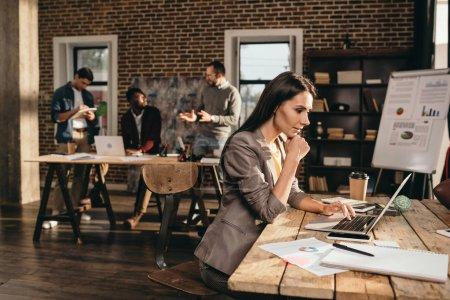 Photo pour Femme d'affaires pensif assis au bureau avec ordinateur portable et travaillant sur le projet au bureau loft avec ses collègues sur fond - image libre de droit