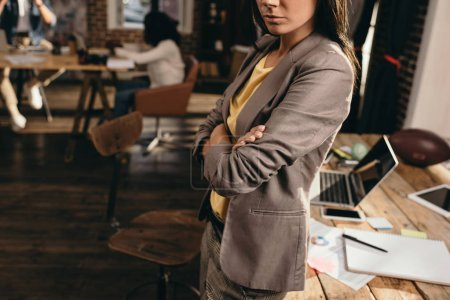Photo for Cropped view of business woman standing at desk in loft office with colleagues on background - Royalty Free Image