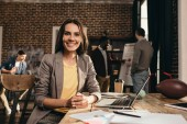 smiling business woman sitting at desk with laptop and working on project at loft office with colleagues on background