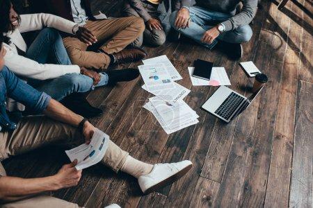 Photo pour Vue élargie du groupe multiethnique de collègues assis sur le plancher et travaillant ensemble sur un nouveau projet - image libre de droit