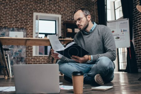 concentrated casual businessman sitting on floor with computer and working on project in modern loft office