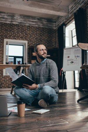 Photo pour Homme d'affaires décontractée assis sur le plancher avec ordinateur et travaillant sur le projet au bureau loft moderne - image libre de droit