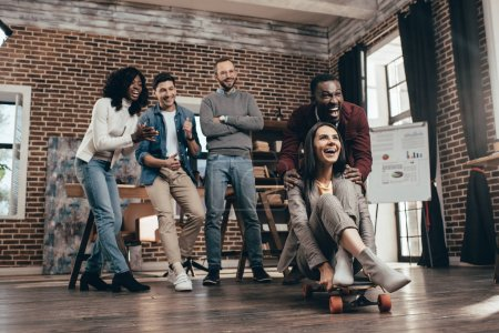 cheerful group of multiethnic coworkers having fun with skateboard in loft office