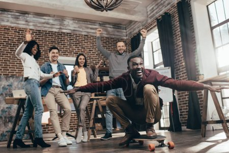 group of happy multiethnic coworkers having fun with skateboard in loft office