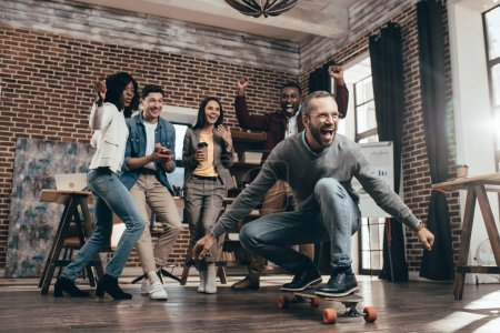 group of multiethnic coworkers having fun with skateboard in loft office
