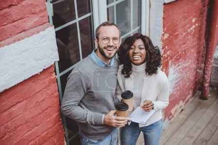 Photo pour Collègues multiethniques regardant la caméra, souriant et prenant un café - image libre de droit