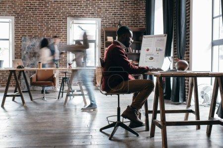 Photo pour Casual homme d'affaires africain-américain travaillant au bureau avec des collègues en mouvement flou au bureau loft moderne - image libre de droit
