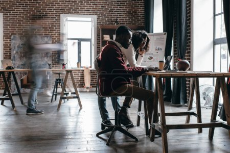 african american couple of casual businesspeople working at desk with colleagues in motion blur in modern loft office