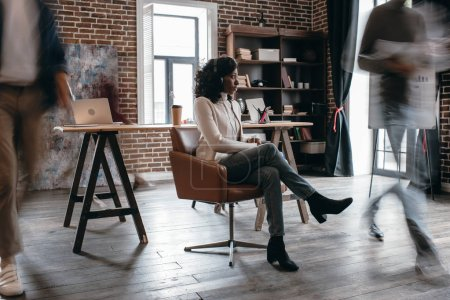 african american businesswoman in heaphones sitting on chair with colleagues in motion blur in modern loft office