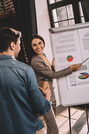 Photo pour Couple enthousiaste de collègues discutant du projet en utilisant le graphique dans le bureau loft - image libre de droit