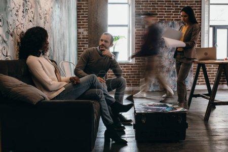 Photo pour Couple multiethnique de gens d'affaires décontractés assis sur le canapé avec des collègues en mouvement flou au bureau loft moderne - image libre de droit