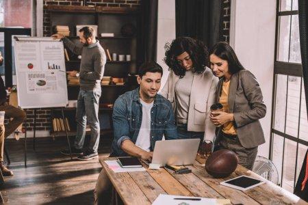 Photo pour Enthousiastes hommes d'affaires occasionnels en utilisant un ordinateur portable et de travailler ensemble dans le bureau loft - image libre de droit