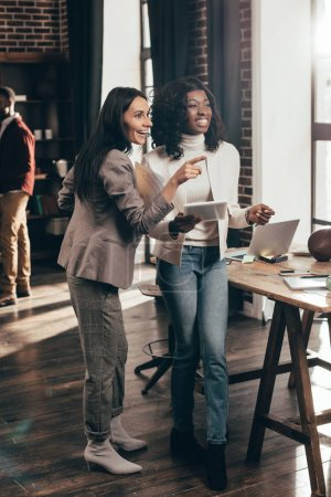 multiethnic couple of business women smiling and working together in loft office with colleagues on background