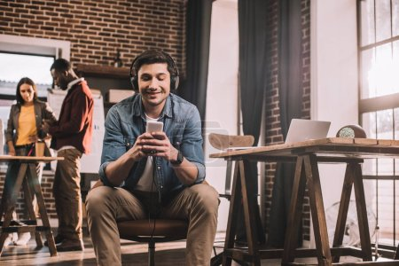 casual smiling businessman using smartphone with multiethnic group of working colleagues behind in modern loft office