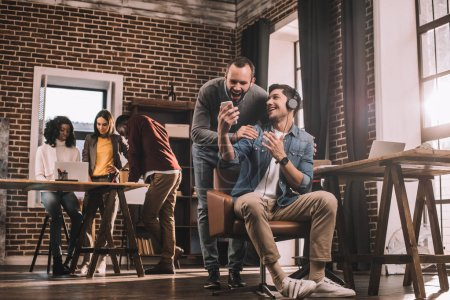 two smiling men using smartphone with multiethnic group of casual businesspeople in modern loft office behind