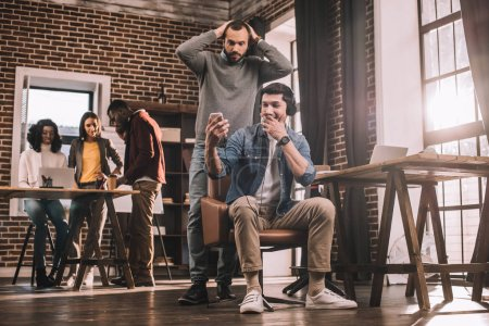 two surprised men using smartphone with multiethnic group of casual businesspeople working in modern loft office behind