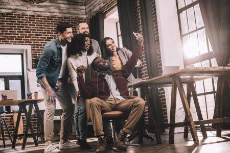 Photo pour Groupe de collègues joyeux prenant selfie en utilisant un smartphone dans le bureau loft avec rétro-éclairé - image libre de droit