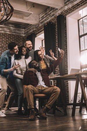 Photo pour Groupe de collègues multiethniques joyeux prenant selfie en utilisant un smartphone dans le bureau loft avec rétro-éclairé - image libre de droit