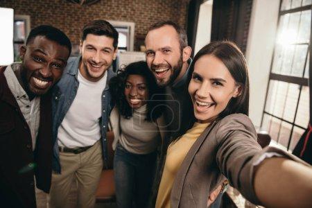 Photo pour Point de vue de la caméra du groupe de collègues joyeux prenant selfie en utilisant un smartphone - image libre de droit
