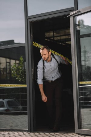male detective leaving the building where the crime occurred