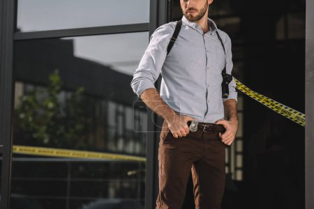 male detective standing with arms akimbo