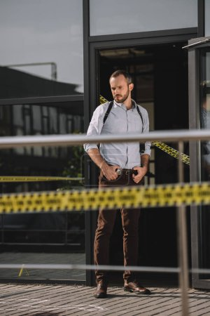 male detective thoughtfully looking at crime scene