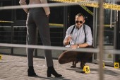 sitting male detective in sunglasses smoking and looking at crime scene with standing partner near him