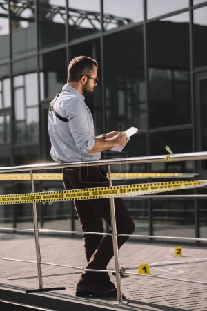 back view of male detective in sunglasses making notes