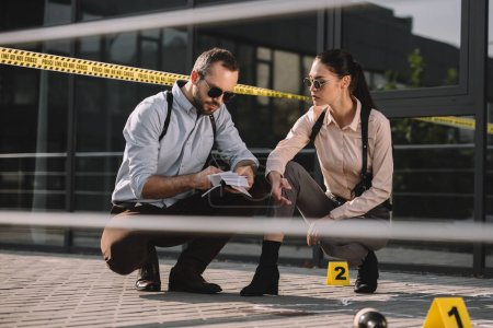 male and female detectives sitting and making some notes in notebook