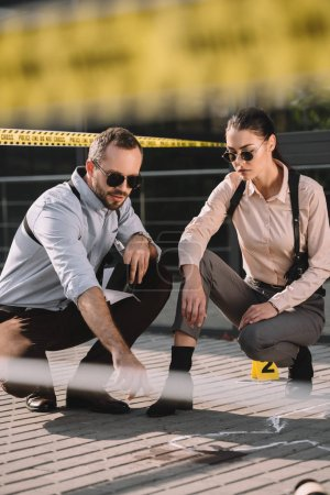 male and female detectives sitting and looking at chalk line at crime scene