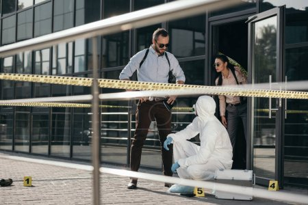 detectives and criminologist  in protective suit and latex gloves communicating at crime scene