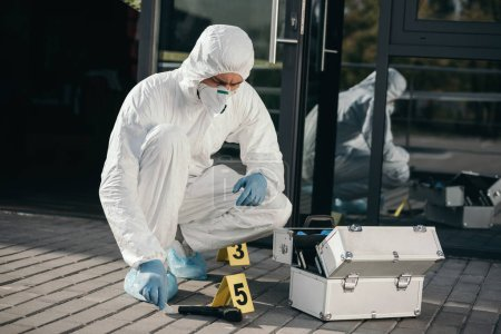 male criminologist in protective suit and latex gloves sitting near evidence gun