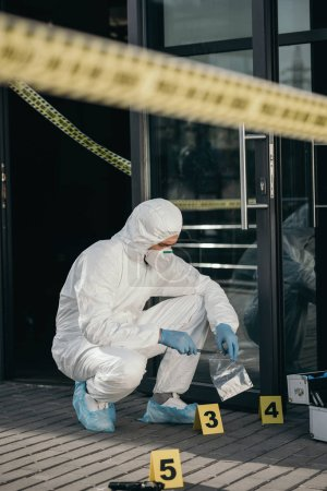 male criminologist in protective suit and latex gloves packing evidence with wizzles at crime scene