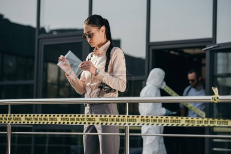 Photo for Female detective standing and looking at evidence in package - Royalty Free Image