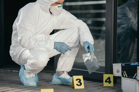 male criminologist in protective suit and latex gloves packing evidence at crime scene