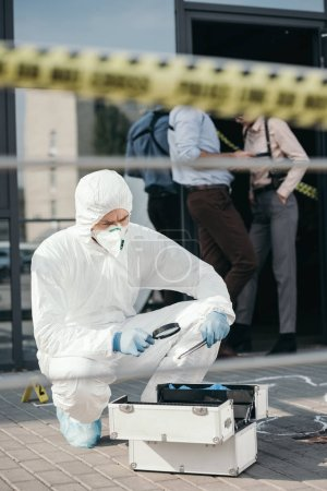 male criminologist in protective suit and latex gloves looking through a magnifier at important evidence