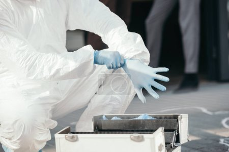 partial view of criminologist wearing latex gloves