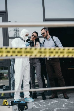 Photo for Criminologist showing photo from crime scene to two detectives - Royalty Free Image