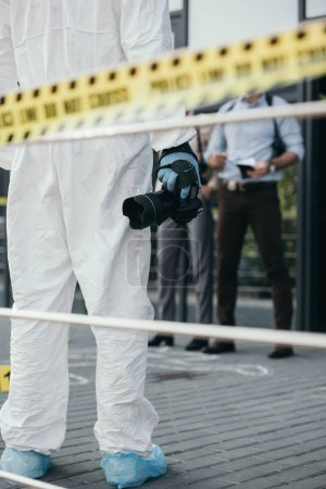 Photo for Cropped view of criminologist in protective suit and latex gloves with camera at crime scene - Royalty Free Image
