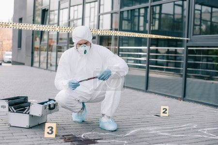 Photo for Male criminologist in protective suit and latex gloves explore the murder weapon at crime scene - Royalty Free Image