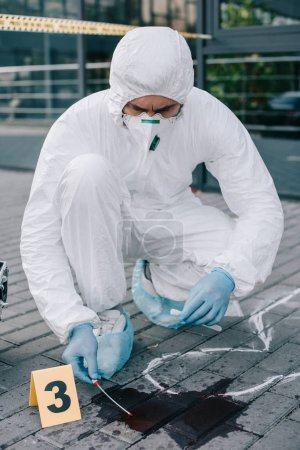 male criminologist in protective suit  taking a blood sample